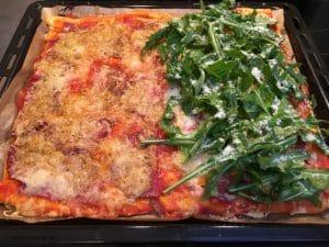 Selbstgemachte Pizza mit Rucola und Parmesan