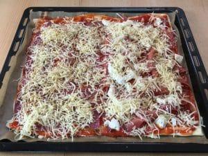 Selbstgemachte Pizza mit Salami, Schinken und Käse belegt