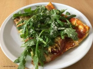 Stück Selbstgemachte Pizza mit Rucola und Parmesan