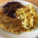 Panierte Schnitzel mit Bandnudeln, Rotkohl und Rahmsoße