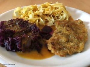 Panierte Schnitzel mit Bandnudeln, Rotkohl und Rahmsosse - Nahaufnahme