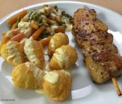 Schweinefiletspieße mit Kroketten, Erbsen, Möhrchen und Soße Hollandaise