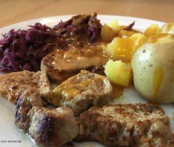 Schweinemedaillons mit Pellkartoffeln, Rotkohl und Soße.