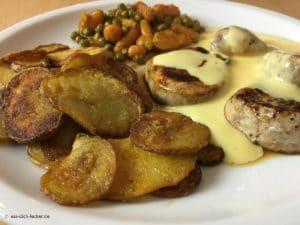 Schweinemedaillons mit Bratkartoffeln, Erbsen und Möhrchen und Soße Hollandaise in Nahaufnahme