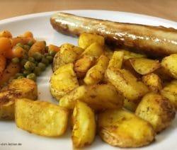 Geflügelbratwurst, Kartoffelspalten mit Erbsen und Möhren in Nahaufnahme