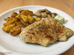 Putenschnitzel mit Kartoffelspalten und Champignons in Nahaufnahme