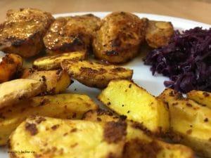 Schweinefiletspieße mit Kartoffelspalten und Rotkohl in Nahaufnahme