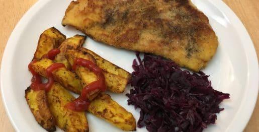 Panierte Schnitzel mit Kartoffelspalten und Rotkohl