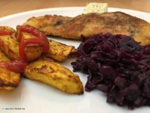 Panierte Schnitzel mit Kartoffelspalten und Rotkohl in Nahaufnahme