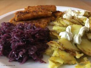 Fischstäbchen mit Bratkartoffeln und Rotkohl in Nahaufnahme