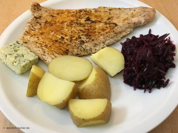 Putenschnitzel mit Pellkartoffeln und Rotkohl auf einem weissen Teller serviert