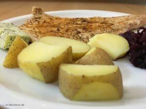 Putenschnitzel mit Pellkartoffeln und Rotkohl in Nahaufnahme auf einem weissen Teller serviert
